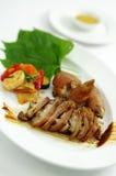 有莲花和kimchi的烤猪` s腿在白色盛肉盘 库存照片