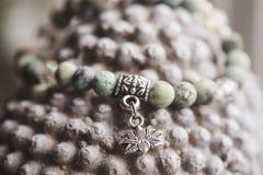 有莲花垂饰的自然绿松石石头瑜伽镯子 库存照片