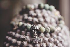 有莲花垂饰的自然绿松石石头瑜伽镯子 图库摄影