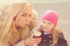 有获得一个乐趣喝从同一纸杯的女儿的逗人喜爱的年轻母亲奶昔 库存照片