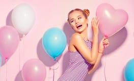 有获得五颜六色的气球的秀丽快乐的十几岁的女孩乐趣 库存图片