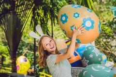 有获得兔宝宝的耳朵的美丽的少妇乐趣用传统复活节彩蛋寻找,户外 庆祝复活节假日 免版税图库摄影