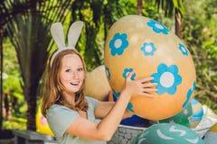 有获得兔宝宝的耳朵的美丽的少妇乐趣用传统复活节彩蛋寻找,户外 庆祝复活节假日 免版税库存图片