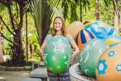 有获得兔宝宝的耳朵的美丽的少妇乐趣用传统复活节彩蛋寻找,户外 庆祝复活节假日 图库摄影