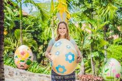 有获得兔宝宝的耳朵的美丽的少妇乐趣用传统复活节彩蛋寻找,户外 庆祝复活节假日 库存图片