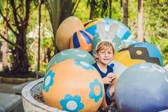 有获得兔宝宝的耳朵的逗人喜爱的小孩男孩乐趣用传统复活节彩蛋寻找,户外 庆祝复活节假日 小孩fi 库存图片