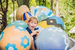 有获得兔宝宝的耳朵的逗人喜爱的小孩男孩乐趣用传统复活节彩蛋寻找,户外 庆祝复活节假日 小孩fi 库存照片