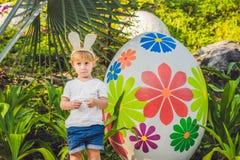 有获得兔宝宝的耳朵的逗人喜爱的小孩男孩乐趣用传统复活节彩蛋寻找,户外 庆祝复活节假日 小孩fi 免版税图库摄影