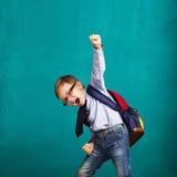 有获得大的背包的微笑的小男孩跳跃和乐趣 库存图片