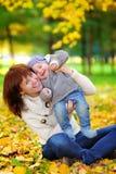 有获得她的小的婴孩的年轻母亲乐趣 免版税库存图片