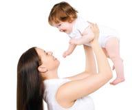 有获得她逗人喜爱的婴孩的愉快的母亲乐趣 图库摄影