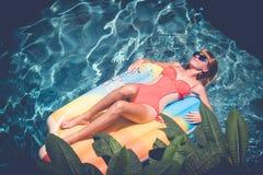 有获得完善的被晒黑的身体的年轻俏丽的妇女说谎在水池的气垫在夏天和乐趣 松弛性感 库存图片