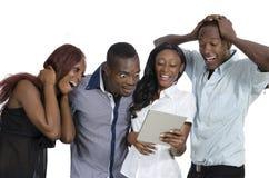 有获得片剂的个人计算机的四非洲青年人乐趣 免版税图库摄影