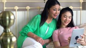有获得的十几岁的女儿的亚裔母亲与片剂的乐趣在 免版税库存照片