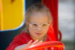 有获得的唐氏综合症的女孩在操场的乐趣 免版税库存照片