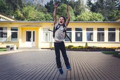 有获得的背包的愉快的男孩跳跃和在学校前面的乐趣 苹果返回黑板消息牛奶学校 图库摄影
