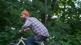 有获得的自行车的年轻人室外乐趣 减速火箭的葡萄酒样式图象 愉快的行家人微笑,当骑自行车在时 股票录像