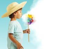 有获得的草帽的男孩与绕环投球法的乐趣 免版税图库摄影