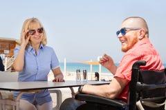 有获得他的妻子的残疾人乐趣,当坐在coffe时 免版税库存图片
