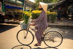 有菊花推进自行车的妇女由市场在越南 免版税库存图片