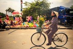 有菊花推进自行车的妇女由市场在越南 免版税图库摄影