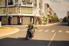 有菊花推进滑行车的女孩沿路在越南 免版税库存图片