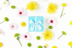 有菊花的一个礼物盒在白色背景 平的位置 库存图片