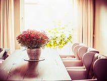 有菊花的美丽的客厅开花在饭桌上的束在窗口背景 图库摄影