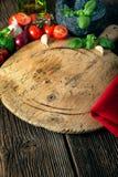 有菜、草本和一台石研磨机的木板 免版税库存图片