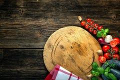 有菜、草本和一台石研磨机的木板 库存照片