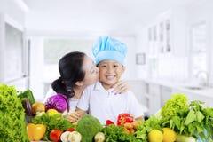 有菜和她的儿子的妇女在厨房里 免版税库存照片