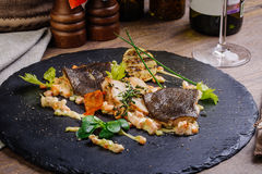 有菜和调味汁特写镜头的被烘烤的鲽内圆角在一块黑石板材 库存照片