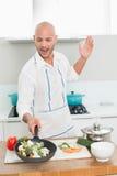 有菜的人在厨房的平底锅 图库摄影