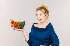 有菜的妇女,消极面孔表示 库存图片
