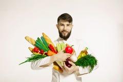 有菜的微笑的英俊的厨师在白色的手上 免版税库存图片