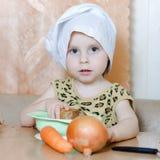 有菜的美丽的逗人喜爱的矮小的厨师 免版税图库摄影