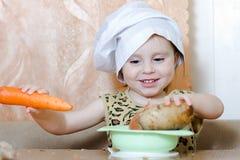 有菜的美丽的逗人喜爱的矮小的厨师 免版税库存照片
