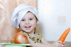 有菜的美丽的逗人喜爱的矮小的厨师 免版税库存图片