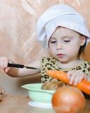 有菜的美丽的逗人喜爱的矮小的厨师 库存图片