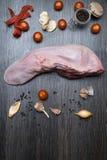 有菜的芹菜,胡椒,大蒜,葱未加工的牛肉或猪肉舌头,在一个切板说谎,在一个黑背景特写镜头 免版税库存照片