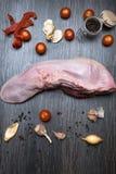 有菜的芹菜,胡椒,大蒜,葱未加工的牛肉或猪肉舌头,在一个切板说谎,在一个黑背景特写镜头 免版税图库摄影