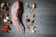有菜的芹菜,胡椒,大蒜,葱未加工的牛肉或猪肉舌头,在一个切板说谎,在一个黑背景特写镜头 免版税库存图片