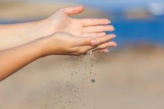 有落通过她的手的沙子的一名妇女 库存照片