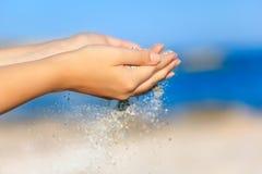 有落通过她的手的沙子的一名妇女 免版税图库摄影