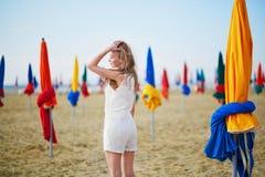 有著名五颜六色的遮阳伞的妇女在多维尔海滩在法国 库存图片