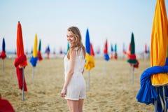 有著名五颜六色的遮阳伞的妇女在多维尔海滩在法国 图库摄影
