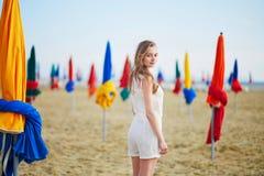 有著名五颜六色的遮阳伞的妇女在多维尔海滩在法国 免版税库存图片