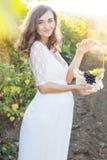 有葡萄篮子的愉快的怀孕的女孩  免版税图库摄影