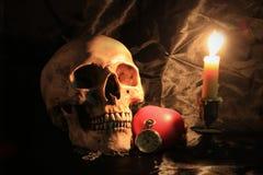 有葡萄酒口袋时钟的人的头骨,红色心脏和蜡烛在黑织品背景、爱和时间概念点燃在静物画 免版税库存图片