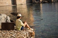 有葡萄酒手提箱选址的旅行家妇女由海边 免版税库存照片